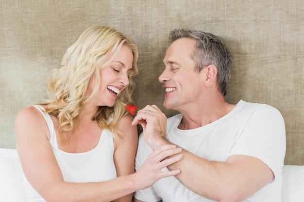 Marido dando um morango para esposa no quarto dela Foto Premium