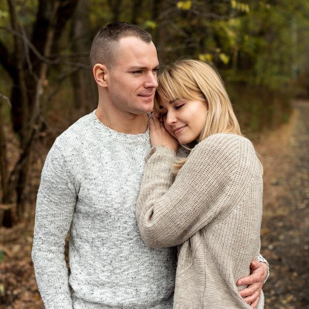 Marido e mulher abraçando na natureza Foto gratuita