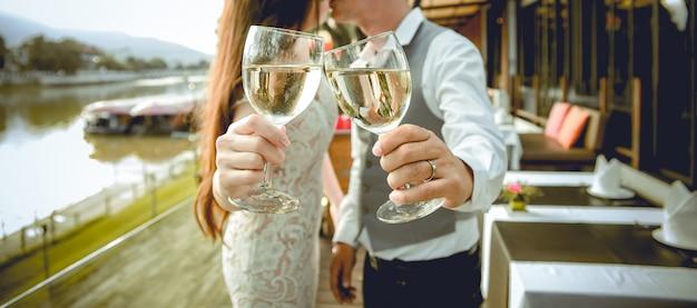 Marido e mulher beijam juntos. há mãos que prendem vidros do vinho no primeiro plano. concentre-se em mãos segurando copos de vinho. profundidade superficial de campo. Foto Premium