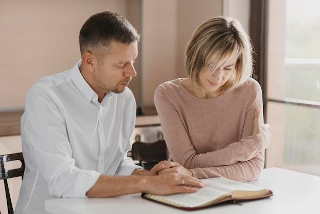 Marido e mulher lendo a bíblia Foto gratuita