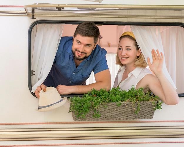 Marido e mulher olhando pela janela de um trailer Foto gratuita