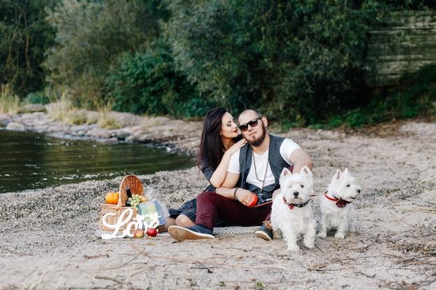 Marido e mulher se divertem na praia com seus dois filhotes brancos Foto Premium