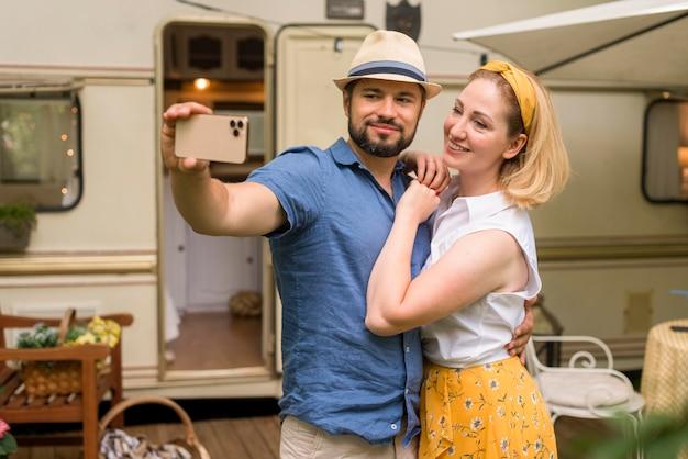 Marido e mulher tirando uma selfie enquanto se abraçam Foto gratuita