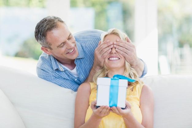 Marido esposa surpreendente com um presente na sala de estar Foto Premium