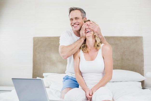 Marido fazendo uma surpresa para a esposa em sua cama Foto Premium