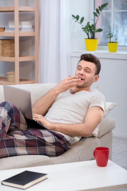 Marido preguiçoso deitado no sofá e bocejando. Foto Premium