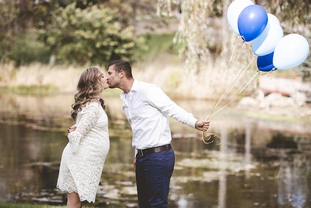 Marido segurando balões e beijando a esposa grávida em um jardim com lago Foto gratuita