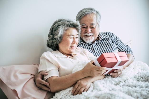 Marido sênior de sorriso que faz a surpresa que dá a caixa de presente a sua esposa no quarto Foto gratuita
