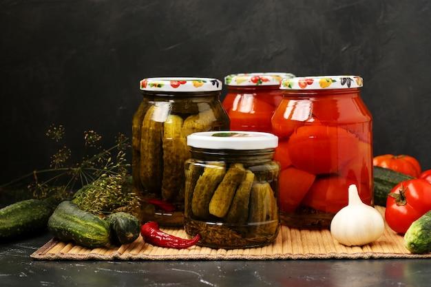 Marinado de pepinos e tomates em frascos em uma mesa em fundo escuro Foto Premium