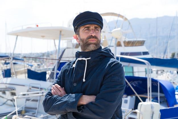 Marinheiro no porto de marina com fundo de barcos Foto Premium