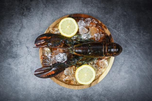 Marisco de lagosta fresca no restaurante de frutos do mar para alimentos cozidos / lagosta crua no gelo e limão em uma vista de mesa de pedra preta Foto Premium