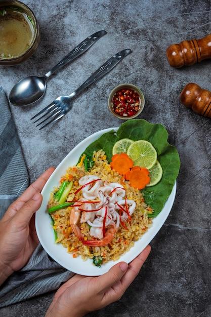 Marisco delicioso arroz frito com camarão, ovos e cebolinhas com sopa. Foto gratuita