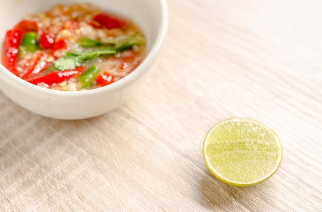 Marisco picante tailandês, mergulhando o molho no fundo de madeira Foto Premium