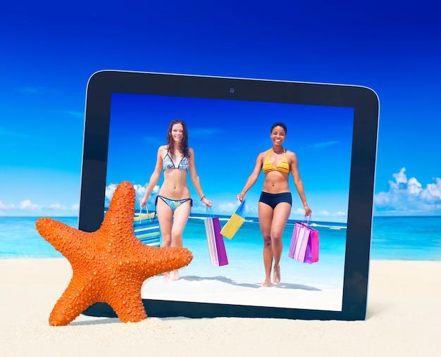 Marque o pc que toma a foto das mulheres com sacos de compras em uma praia tropical. Foto gratuita
