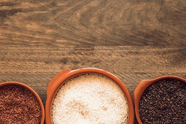 Marrom branco; tigela de arroz vermelho e preto sobre fundo de madeira Foto gratuita