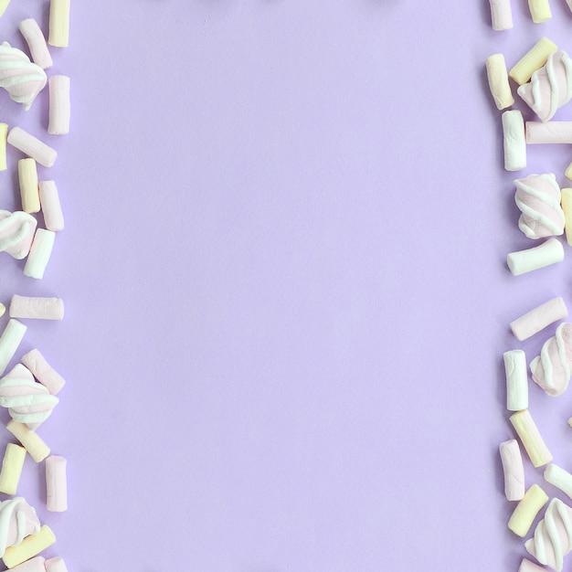 Marshmallow colorido deitado no fundo de papel violeta Foto Premium