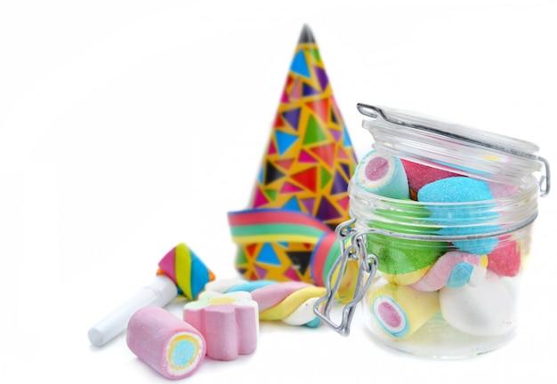 Marshmallow colorido em uma jarra de vidro e favor festa no fundo branco Foto Premium