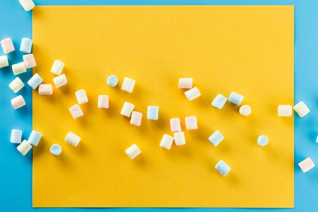 Marshmallow colorido sobre fundo de papel amarelo Foto gratuita