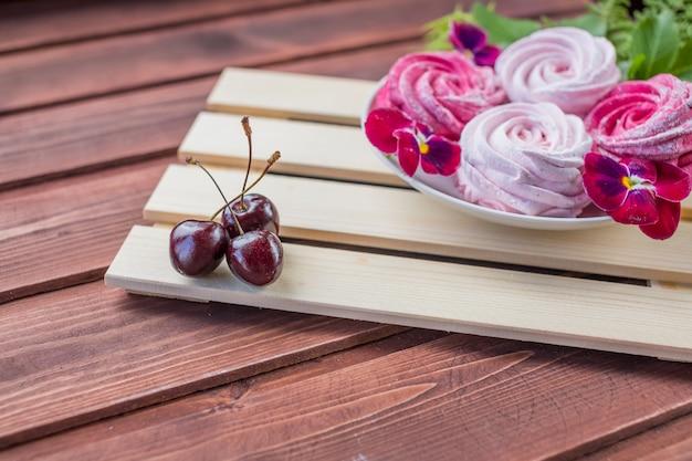 Marshmallow com bagas de cereja e flores sobre fundo claro de madeira Foto Premium