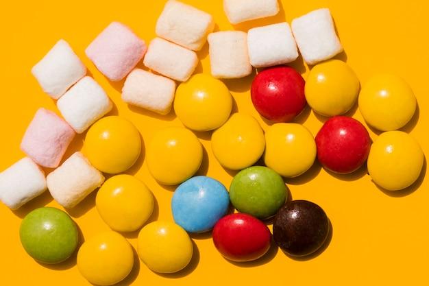 Marshmallow e doces coloridos em fundo amarelo Foto gratuita
