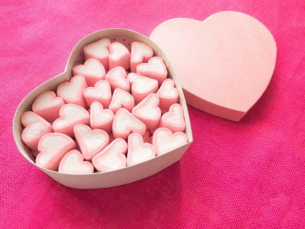 Marshmallow rosa em uma caixa de presente em forma de coração na tela rosa Foto Premium