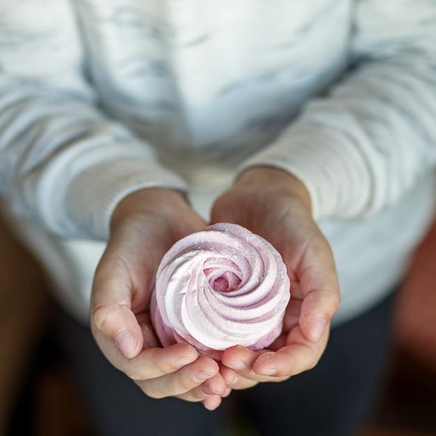 Marshmallows doces delicados nas mãos das crianças. o conceito de comida e doces Foto Premium