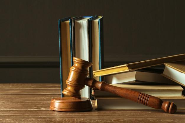 Martelo com livros na velha mesa de madeira Foto Premium