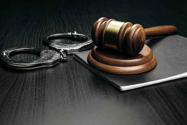 Martelo de juiz com algemas na mesa de madeira Foto Premium