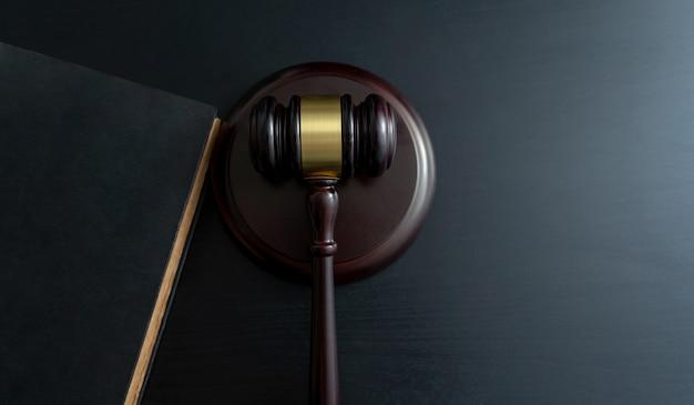 Martelo de juiz com livros na mesa de madeira Foto Premium