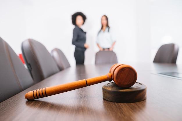 Martelo de juiz na mesa e mulheres afro-americanas no escritório Foto gratuita