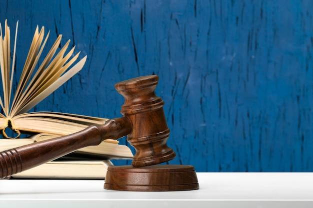 Martelo de madeira e livros sobre a mesa de madeira Foto Premium
