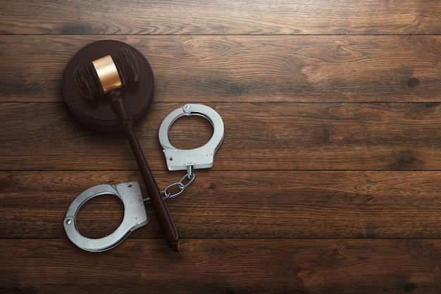 Martelo do juiz e algemas em fundo de madeira Foto Premium
