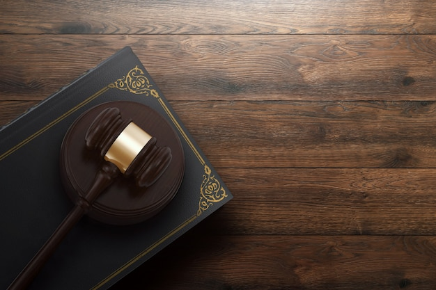 Martelo do juiz e livro sobre fundo de madeira Foto Premium