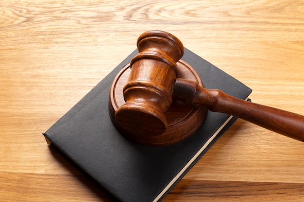 Martelo e livro legal na mesa de madeira Foto Premium
