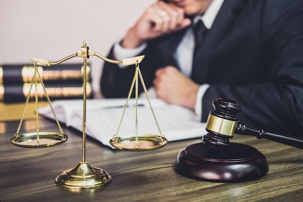Martelo na mesa de madeira e advogado ou advogado masculino trabalhando em um documento Foto Premium