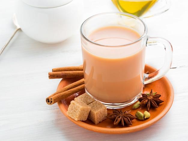 Masala bebida indiana no festival de holi. chá com leite e especiarias em uma caneca de vidro. Foto Premium