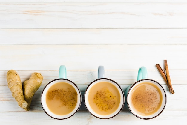 Masala chá em copos de cerâmica com as especiarias de canela e gengibre de inverno Foto Premium