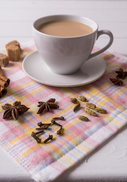 Masala chai chá na xícara, açúcar mascavo, paus de canela, anis e badian Foto Premium