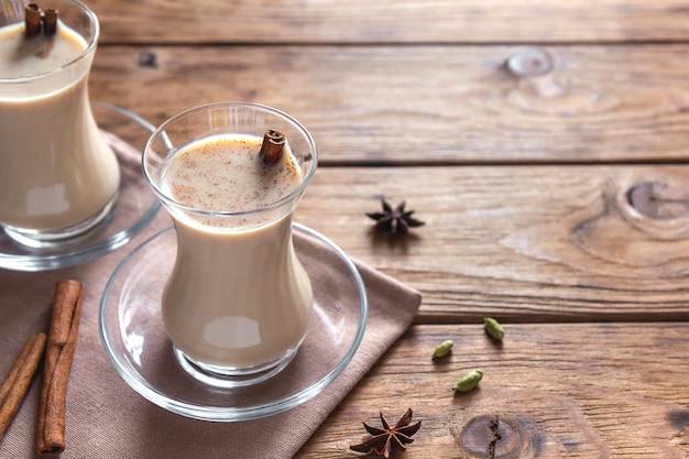Masala chai com canela em copos transparentes em uma mesa de madeira. Foto Premium