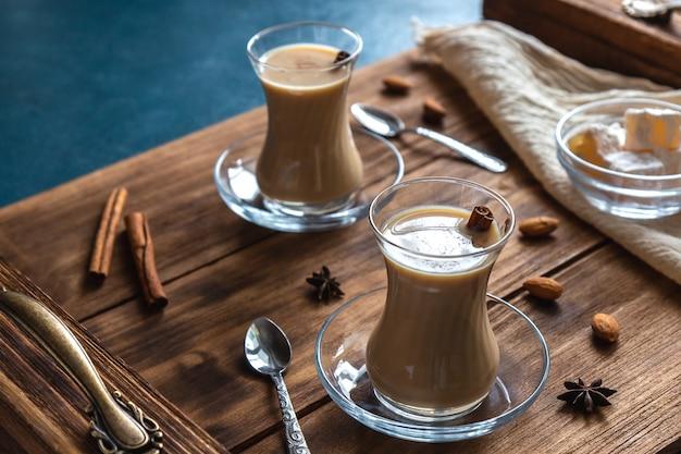 Masala chai com especiarias em copos de vidro Foto Premium