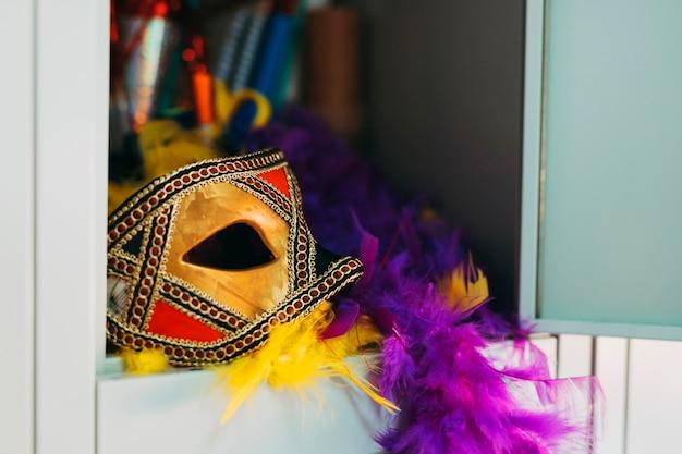 Máscara bonita do carnaval com a boa de pena roxa e amarela no cacifo Foto gratuita