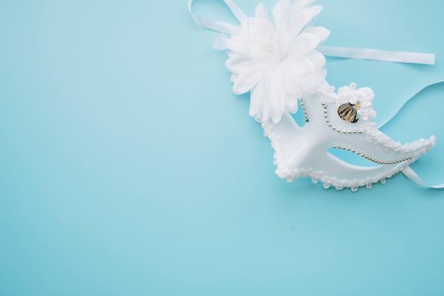Máscara branca elegante em fundo azul Foto gratuita