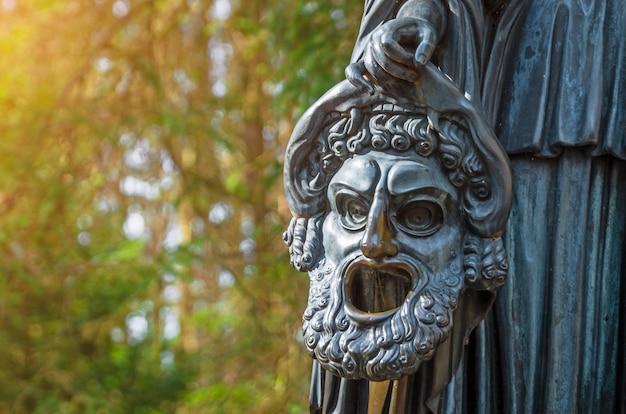 Máscara chorosa de uma escultura de cobre em um parque florestal Foto Premium