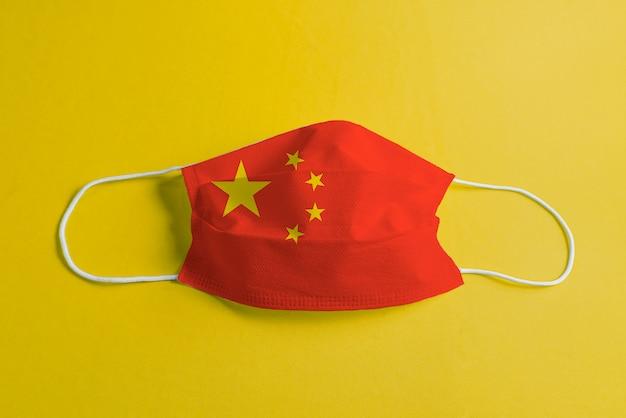 Máscara cirúrgica em fundo amarelo com bandeira da china Foto gratuita
