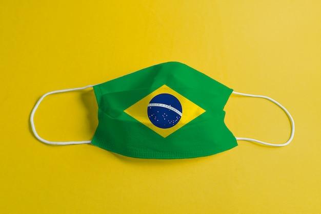 Máscara cirúrgica em fundo amarelo com bandeira do brasil Foto gratuita