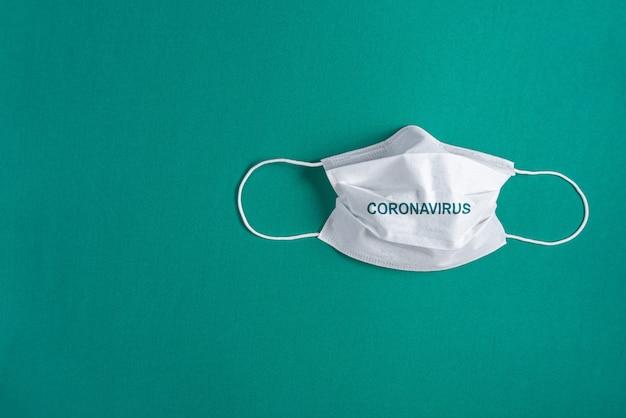 Máscara cirúrgica sobre fundo verde minimalista Foto gratuita