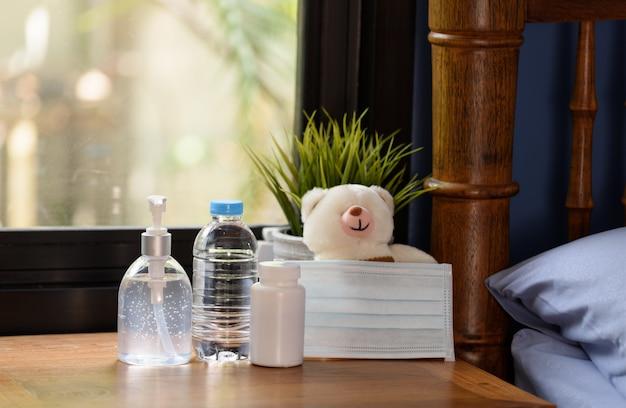 Máscara cirúrgica, ursinho de pelúcia e medicamento na mesa de madeira com natureza verde Foto Premium