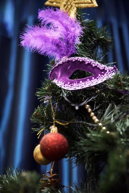 Máscara de carnaval bonito pendurado na árvore de natal Foto Premium