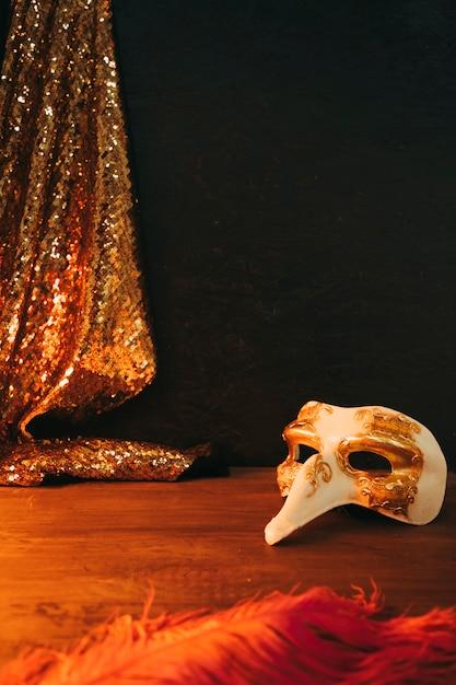 Máscara de carnaval branco e dourado com pena e lantejoulas têxtil contra fundo preto Foto gratuita