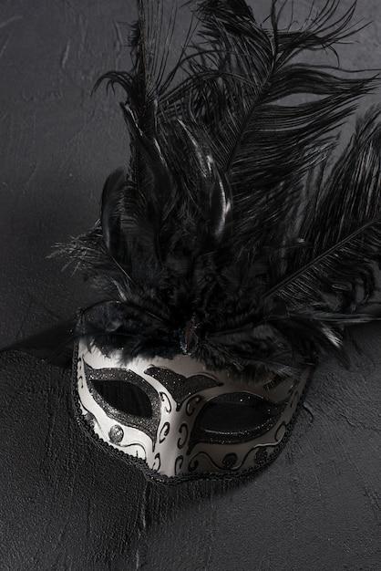 Máscara de carnaval cinza com penas na mesa Foto gratuita